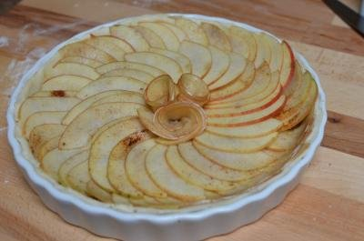 Apple slices placed over the top of the pie to form a swirl shape with a flower inside also made of apple slices