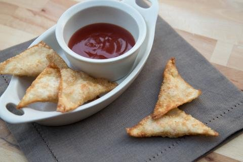 Crunchy puffs in a plate with a little bowl of sweet and sour sauce all on a table