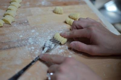 Homemade Gnocchi being rolled on a floured cutting board