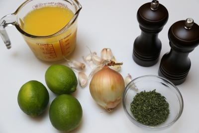 Ingredients on table including; 3 limes, onion, garlic, a measuring cup with orange juice, parsley and salt and pepper