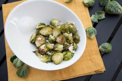 Feta Garlic Brussel Sprouts in a bowl with raw brussels around the plate