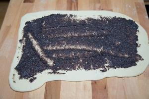 Dough rolled out into a rectangle on a cutting board with poppy seeds spread on it