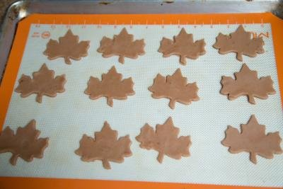 Cookie dough cut into leaf shapes and placed on a baking sheet that is lined with parchment paper