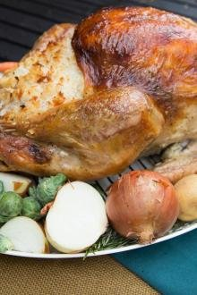 Turkey on a serving tray surrounded with veggies like brussels, onions, potatoes, radishes, onions and carrots