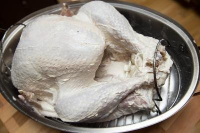 Seasoned turkey in a turkey cooker tray