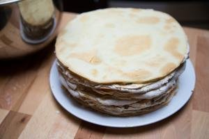 Cake layers with cream between them stacked on a plate