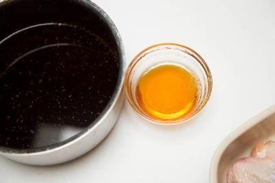 A small bowl of honey next to the pot with the sauce