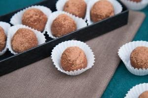 Russian Cake Truffles in cupcake liners on a serving tray and two besides the serving tray