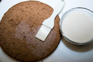 Whipping cream and liquor mixture being placed on each cake layer