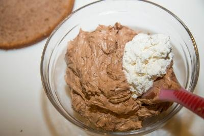 Whipped cream and chocolate mixture being combined in bowl with a spatula