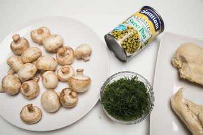 Ingredients on the table include; mushrooms, dill, peas in a can, and 2 chicken breasts