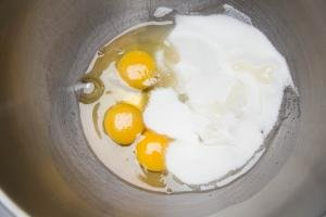3 eggs and sugar in a mixing bowl