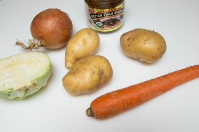 Ingredients on table including; a carrots, 3 potatoes, half a cabbage, an onion and Better then Bouillion beef base