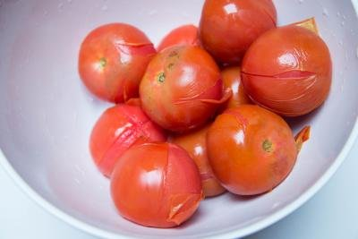 Tomatoes in a bowl with the skin peeling off
