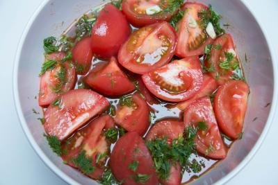 Tomatoes mixed with dill, garlic and marinate in a bowl