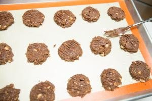 Cookies on baking sheet being flattened with a fork