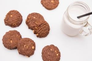 Nutella Cookies spread on a table with milk in a mason jar cup next to them