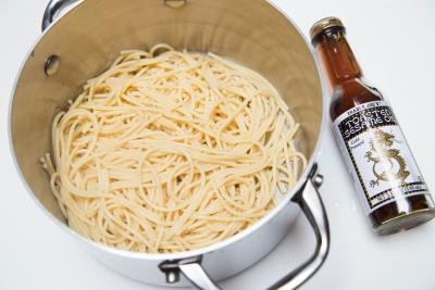 Cooked spaghetti in a pot with sesame oil next to it