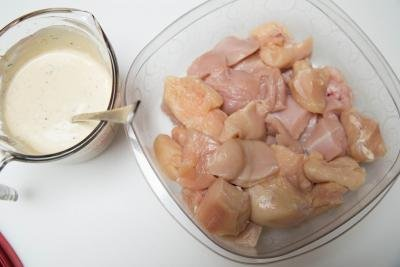 Chicken pieces in container and a marinate in measuring cup