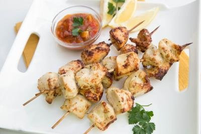 Chicken Kebabs on a plate with lemon slices and a bowl of salsa next to them