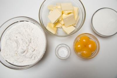 Ingredients in bowls on the table including; 4 egg yolks, butter, flour, sugar and baking powder