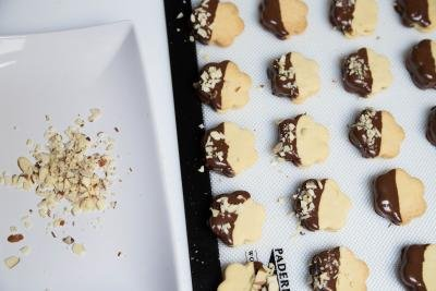 Dulce De Leche Sandwich Cookies dipped into chocolate being sprinkled with crushed almonds