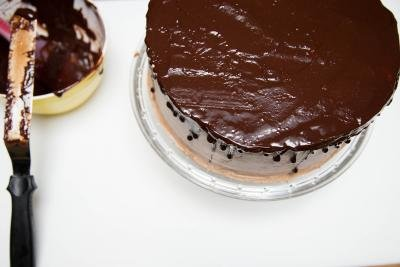 Chocolate ganache spread around the top of the cake to form a flat and even coat