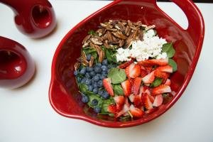 Spinach, blueberries, cut up strawberries, halved walnuts and feta all in a bowl