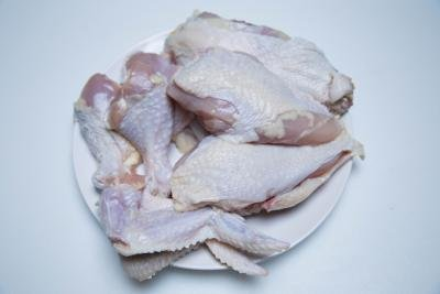 A chicken separated into parts; wings, drumsticks, breasts and thighs