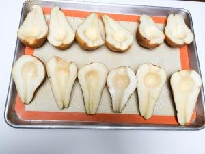 Pears cut in half with the inside taken out and placed on a baking pan that is lined with a silicon mat