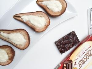 Baked Pears with ricotta cheese mixture filling on a plate and a chocolate bar next to them