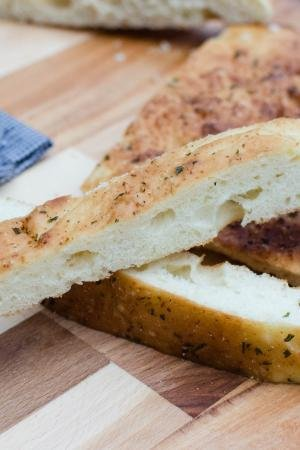 Easy Focaccia Bread cut into long thin slices on a cutting board