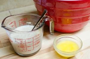 Water and yeast mixed together in a measuring cup and a bowl with melted butter next to it
