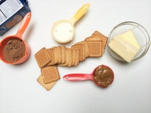 Ingredients on table including; biscuit cookie, 2 sticks of butter in a bowl, cocoa, dulce de leche and condensed milk