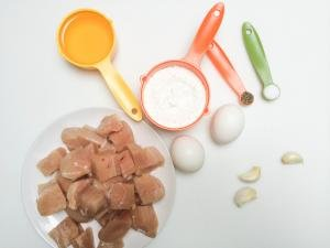 Ingredients on table include; chicken cut into bite size cubes on a plate, 2 eggs, 3 garlic cloves, slat and pepper, cornstarch and oil
