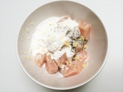 Chicken in a bowl covered in cornstarch, garlic, and salt and pepper