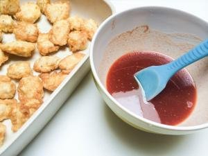baking pan with chicken bites and a bowl with the sauce next to it