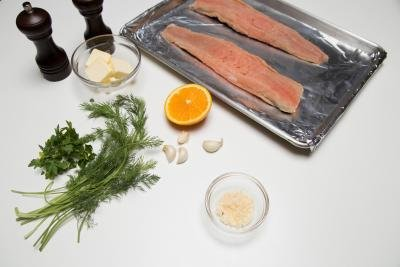 Ingredients on table including; dill, parsley, 4 garlic cloves, orange, butter in a bowl, parmesan cheese, salt and pepper and salmon on a baking pan lined with foil