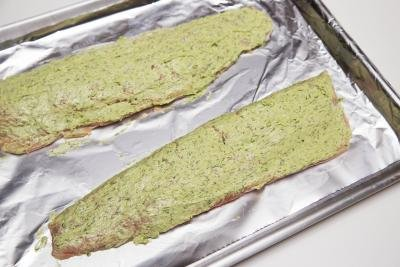 herb butter spread on the top of the salmon that is on the baking pan lined with foil