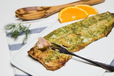 Baked Herbed Salmon on a plate, with an orange slice on it and a fork in it