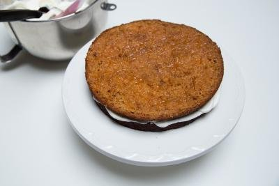 Cake being layered as following; sponge, jam and cream and repeated