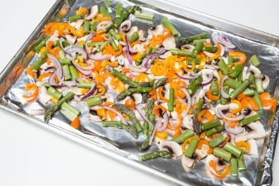 Veggies cut up and spread out on a baking sheet that is lined with foil