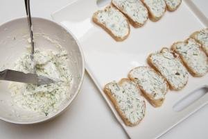 Cream cheese and dill mixture being spread on bread slices that are placed in rows on a plate