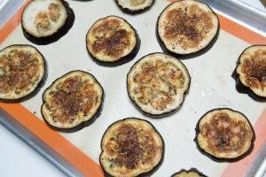 Cooked eggplant slices laid out on a baking sheet lined with a silicon mat with oil and salt sprinkled on top of them