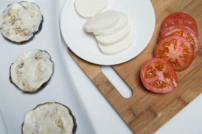 Eggplant slices with garlic mayo on them and a cutting board with tomato and mozzarella slices