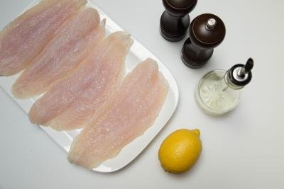 On the table there is a plate with 4 fish fillets, a lemon, oil, and slat and pepper