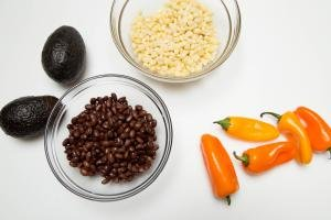 Ingredients on table including; a bowl of black beans, a bowl of corn, 2 avocados and 5 mini peppers
