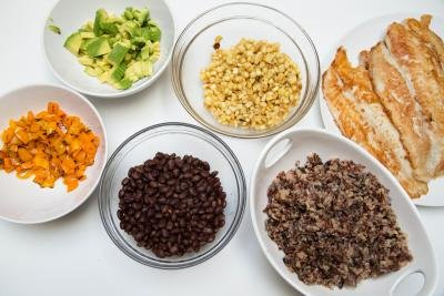 5 plates on the table; one with black beans, one with diced mini bell peppers, one with sautéed corn, one with diced avocado, one with cooked quinoa and rice blend and one with fish fillets