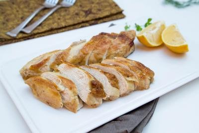 Beer Roasted Chicken cut up into slices layer out in rows on a plate with lemon slices