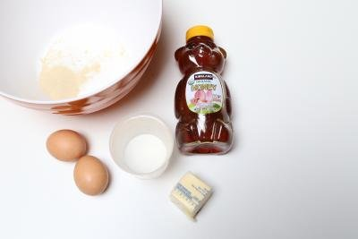 A large bowl with yeast and water; honey, 2 eggs, butter and salt laying besides the bowl